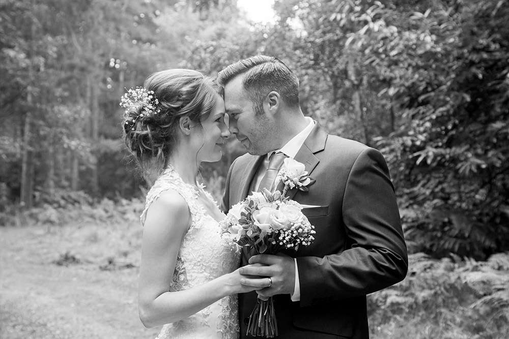 Norfolk Wedding Photography of a Bride & Groom starring into each other eyes in the woods at Sandringham in Norfolk