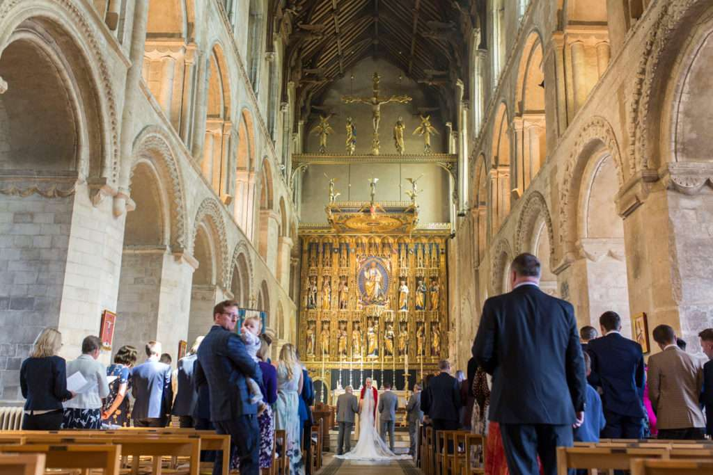 Inside Wymondham Abbey at the wedding ceremony of Susanna & Matt. Bride & groom stood at the alter with the vicar.