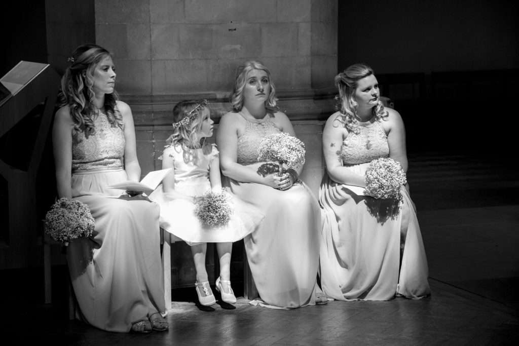 Bridesmaids sat in the sunlight at Wymondham Abbey during the wedding ceremony