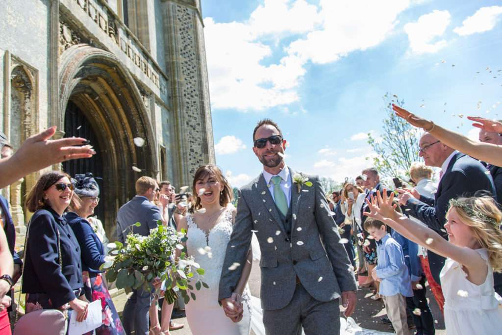 Bride & Groom walking through confetti at Wymondham Abbey in Norfolk