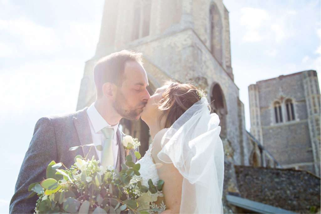 Bride & Groom kissing in front of Wymondham Abbey in Norfolk