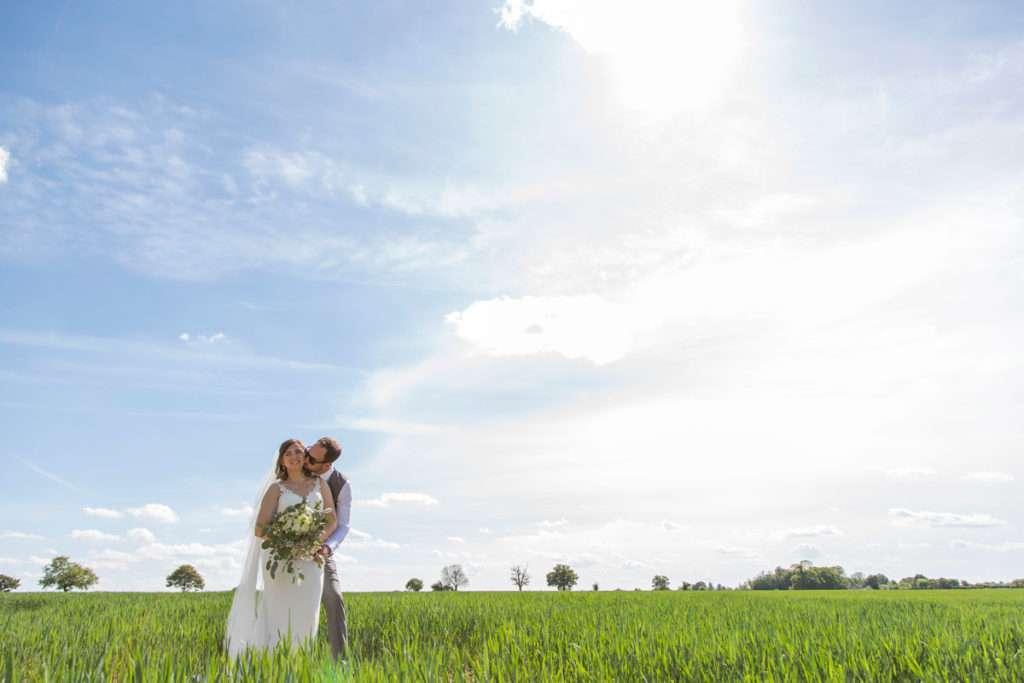 Bride & Groom cuddling in a field with blue sky