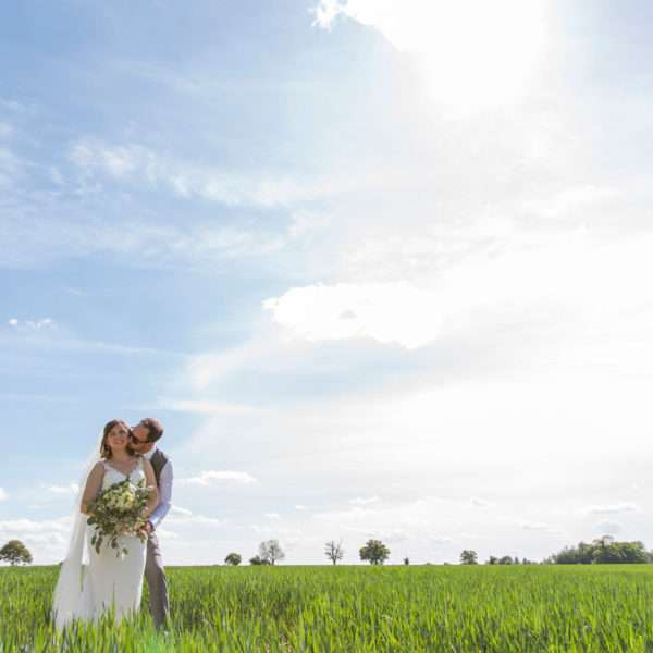 Bride & Groom cuddling in a field with blue sky
