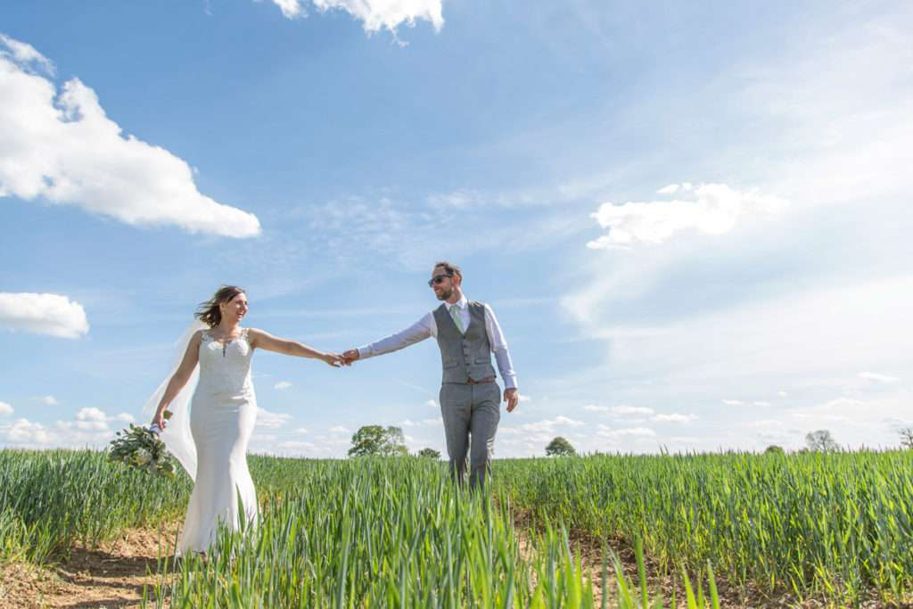 Bride & Groom walking through corn field holding hands at Low Barn Farm Fundenhall in Norfolk