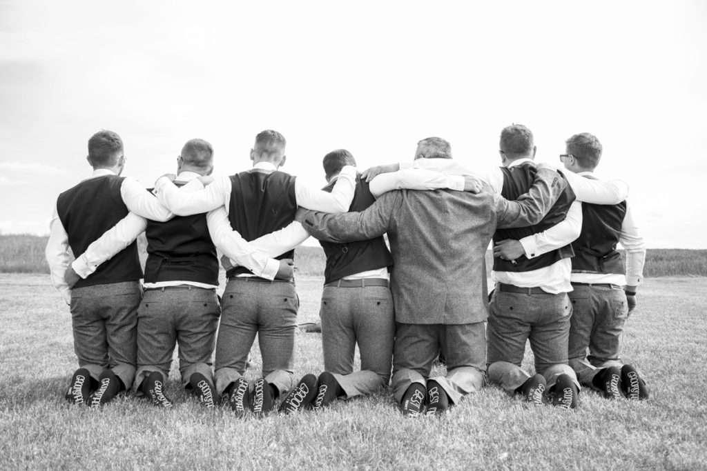 Grooms party kneeling in field showing off their personalised wedding socks