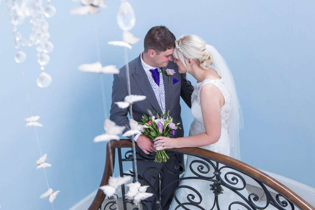 Bride & Groom standing on the stairs at Kimberley Hall in the Bufferfly room