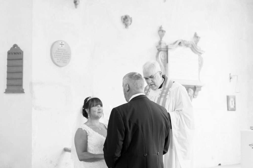 Bride & Groom stood at the alter with the vicar at Old Lakenham Church in Norwich