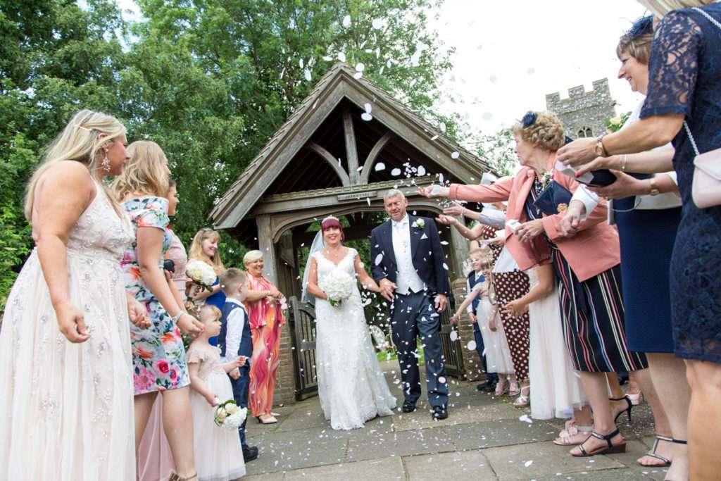 Bride & Groom walking through confetti after their wedding at Old Lakenham Church in Norwich, Norfolk