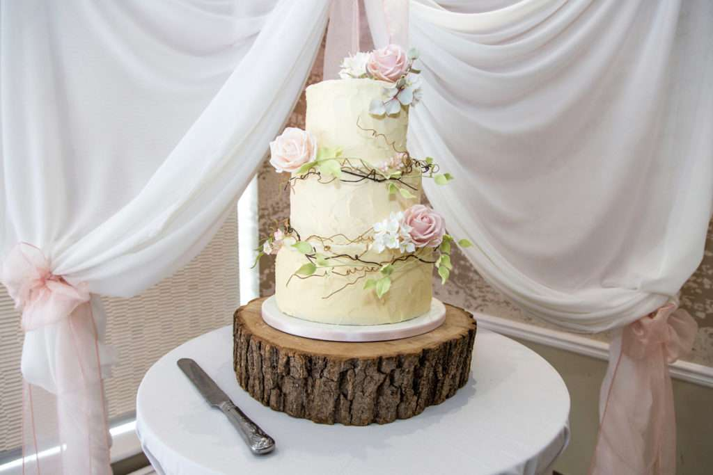 Beautiful wedding cake decorated with flowers on a log slice