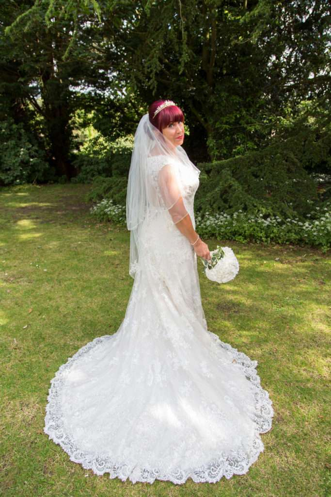 Bride with her bouquet stood in the gardens at The Oaklands Hotel in Norwich