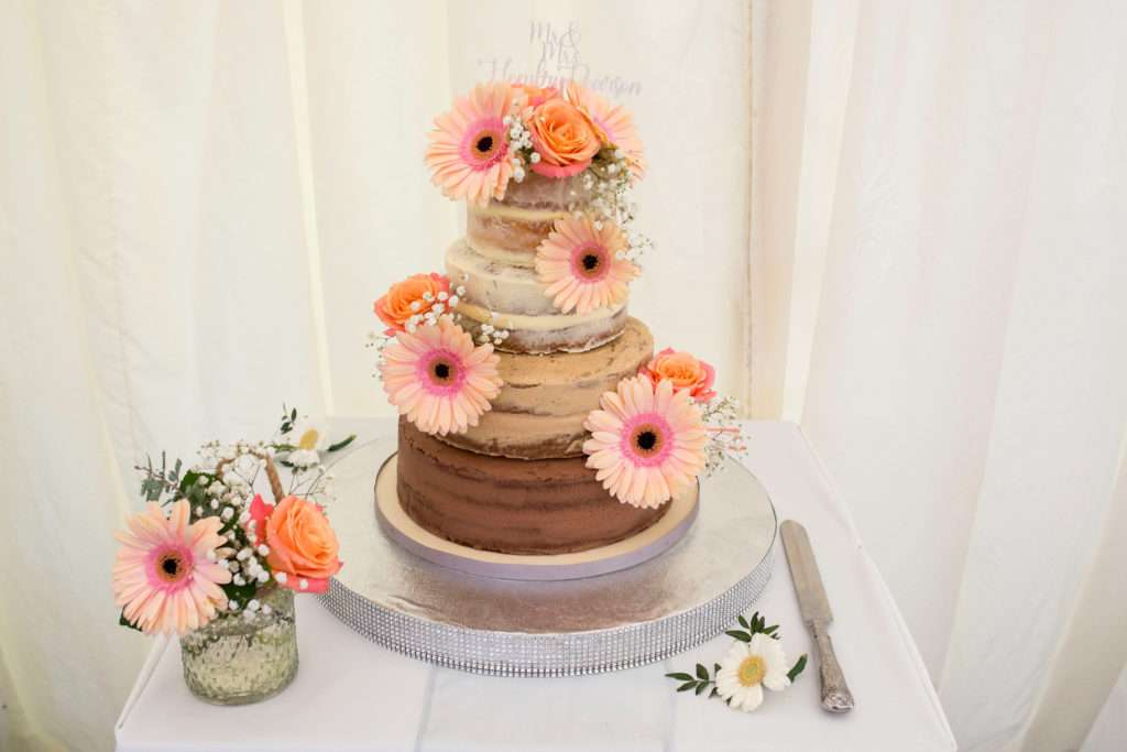Wedding cakes with peach flowers on it. Cakes is on a table with cake knife and a small vase with peach flowers in it.