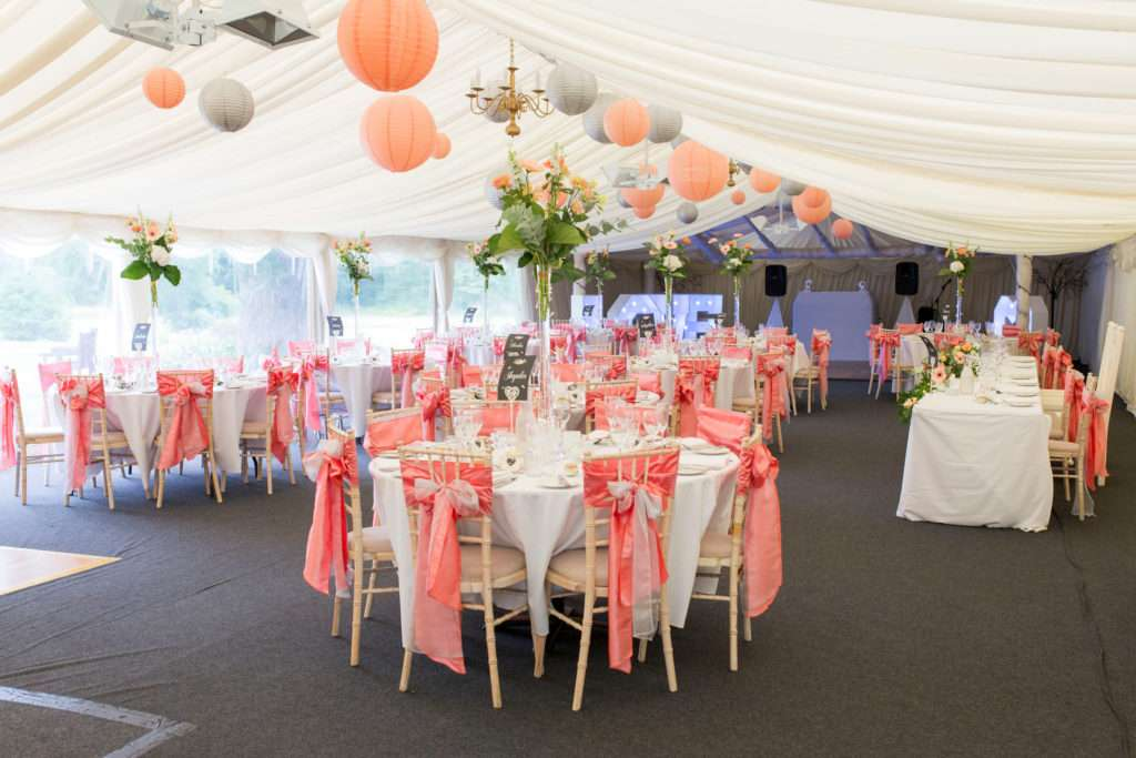Lenwade House Hotel marquee dressed for a wedding with tables and chairs, hanging lanterns in shades of peach