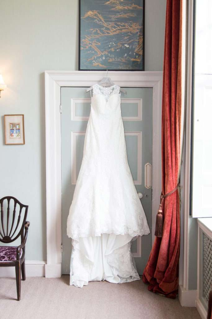 Bride's wedding dress hung infront of door inside Kimberley Hall