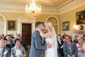 Bride & Groom kissing during their wedding ceremony at Kimberley Hall