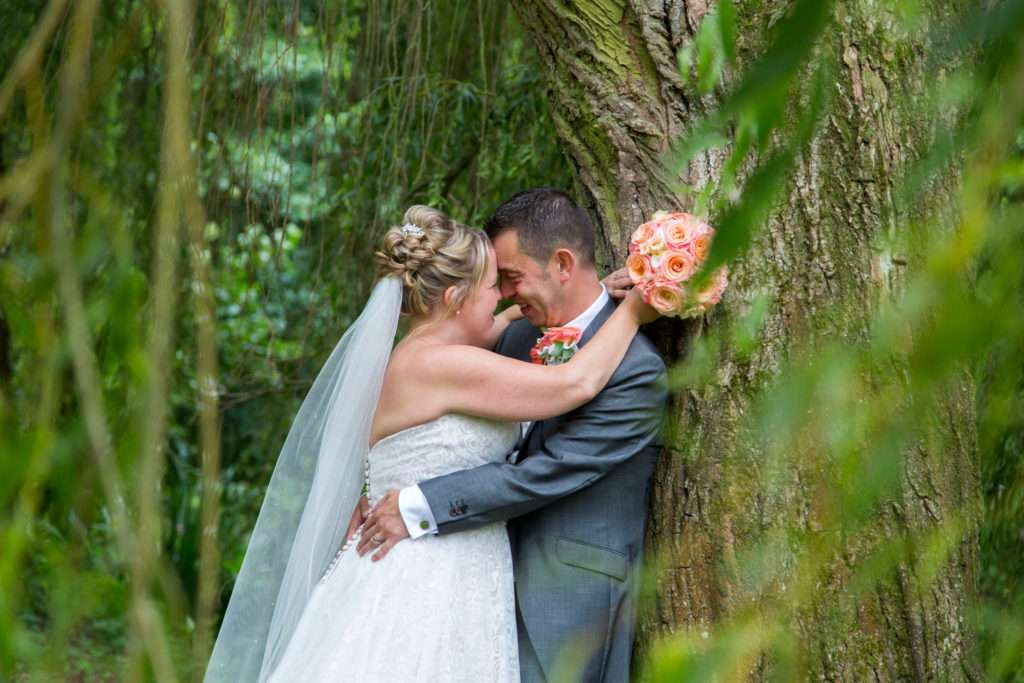 Bride & Groom in each others arms leaning against a tree at Lenwade House Hotel in Norfolk