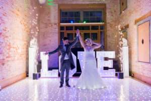 Bride & Groom on the dancefloor having their first dance at Kimberley Hall. LOVE letters in the background. Norfolk Wedding Photography