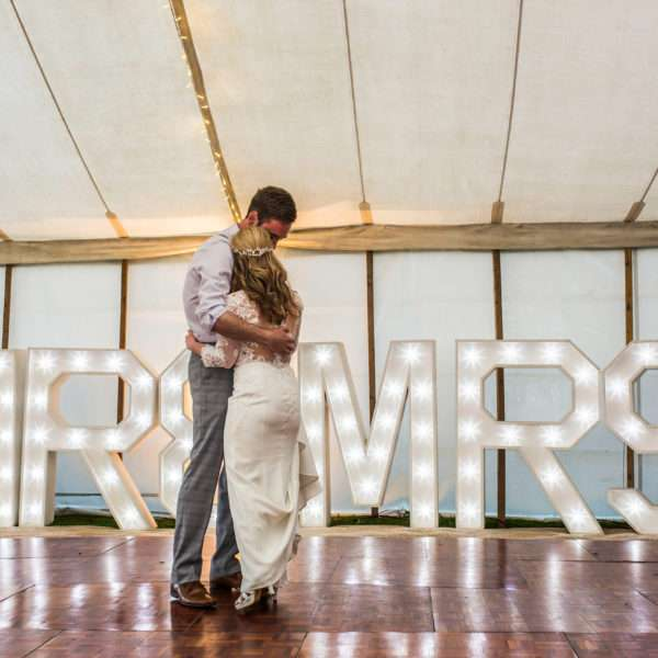 Bride & Groom having their first dance in a marquee at Coldham Hall in front of Mr & Mrs light up letters