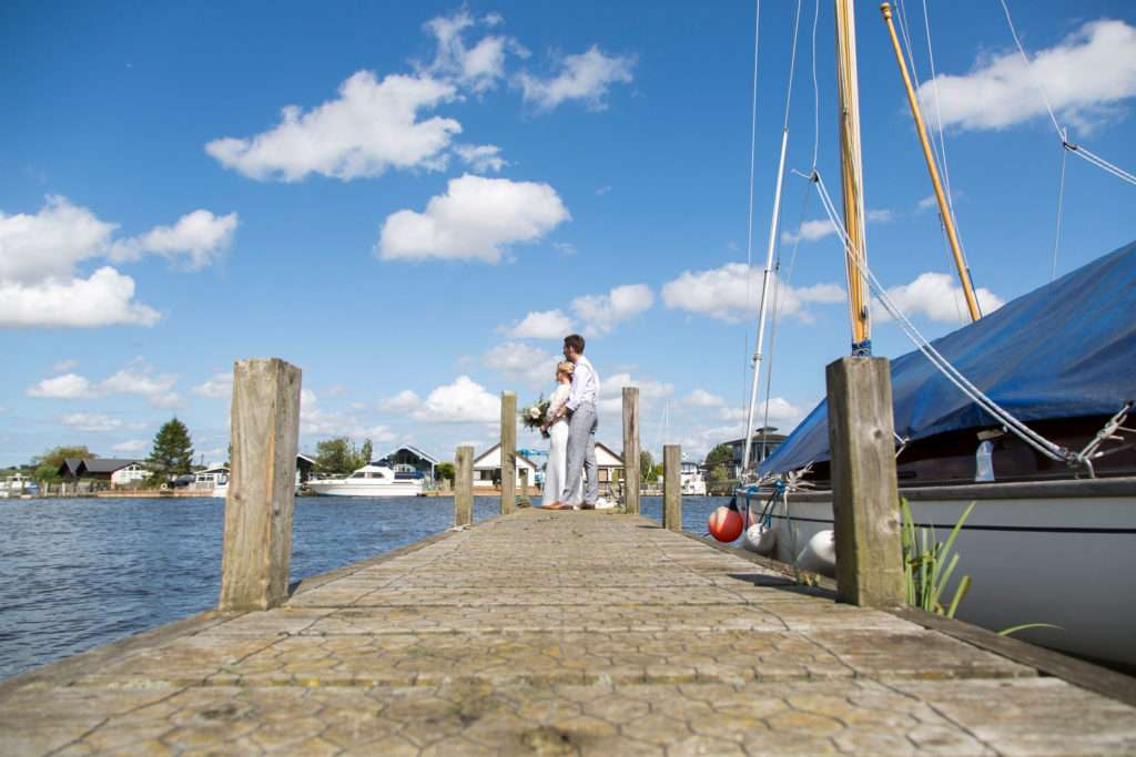Bride & Groom standing on the pier at Coldham Hall with the river in the background