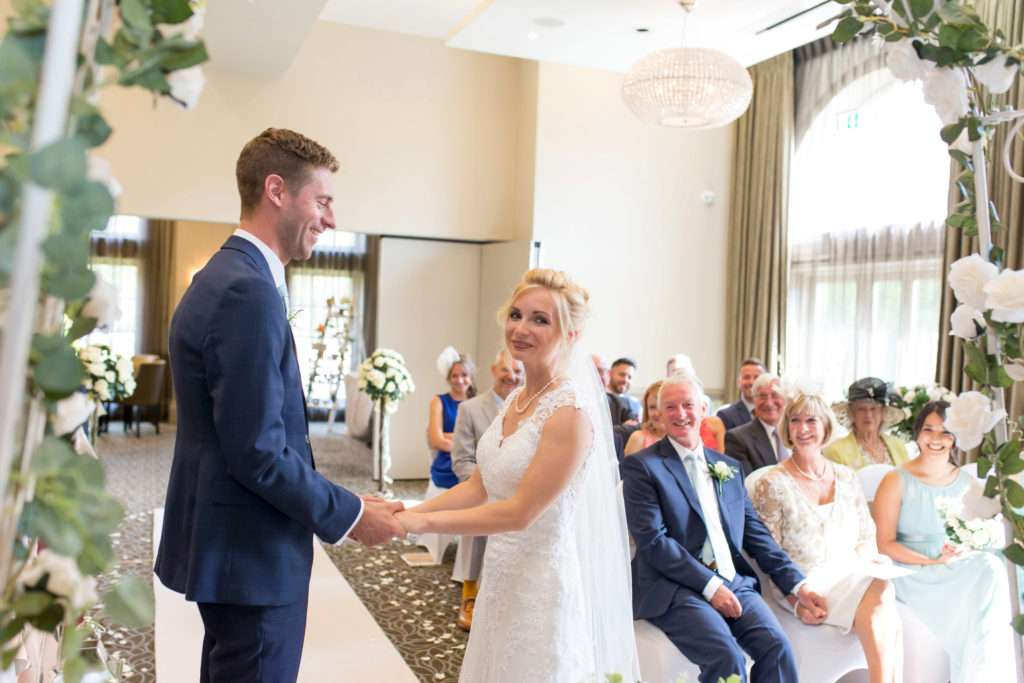 Bride & Groom holding hands during their wedding ceremony at Bedford Lodge in Newmarket, Suffolk.