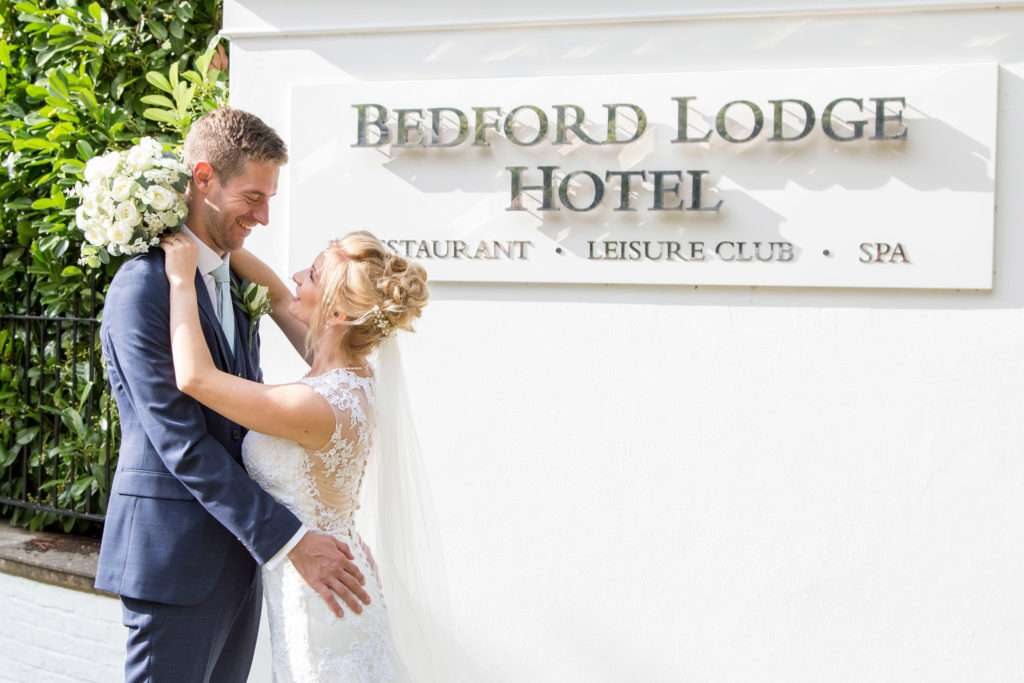 Bride & Groom with their arms round each other, stood outside at Bedford Lodge in Newmarket, Suffolk