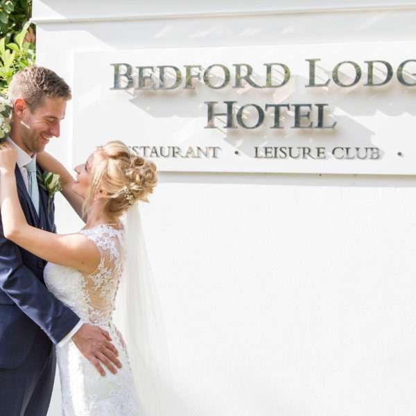 Bride & Groom with arms round each other infront of the sign for Bedford Lodge Hotel