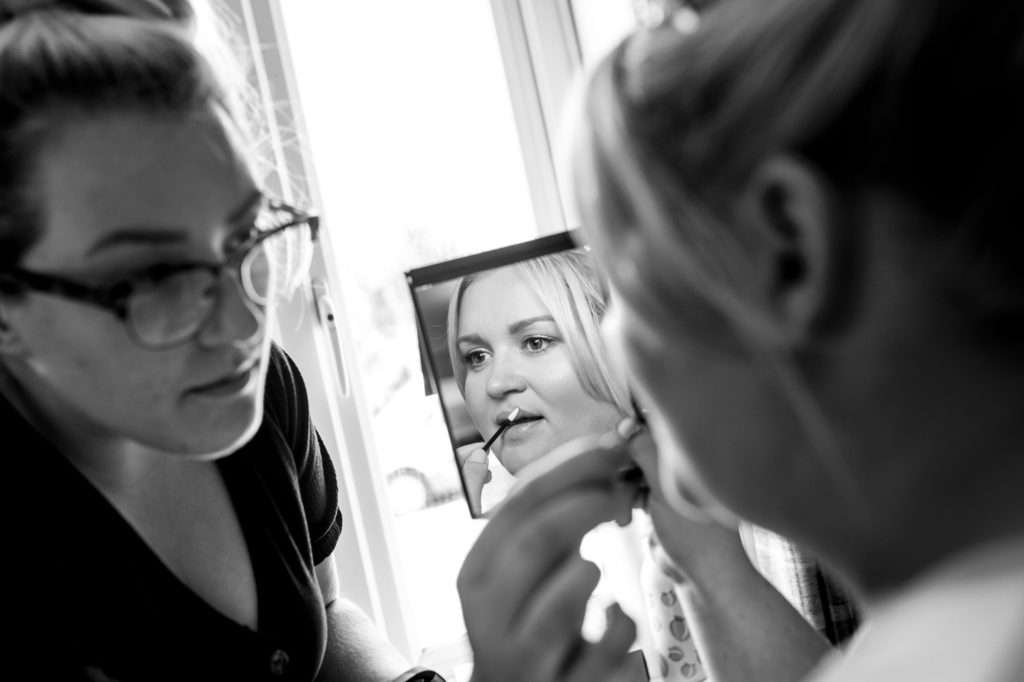 bride having her make up done before her wedding
