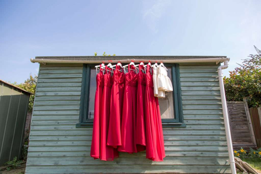 Red Bridesmaids dresses hanging on the side of a building