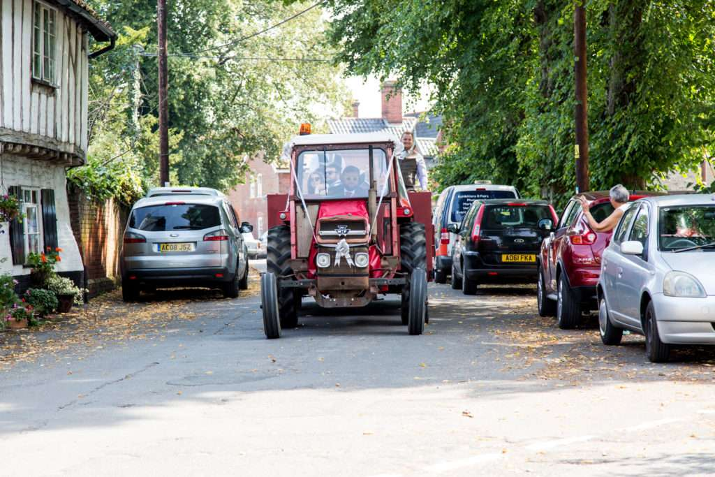 Vintage tractor with groom & party driving through Banham in Norfolk
