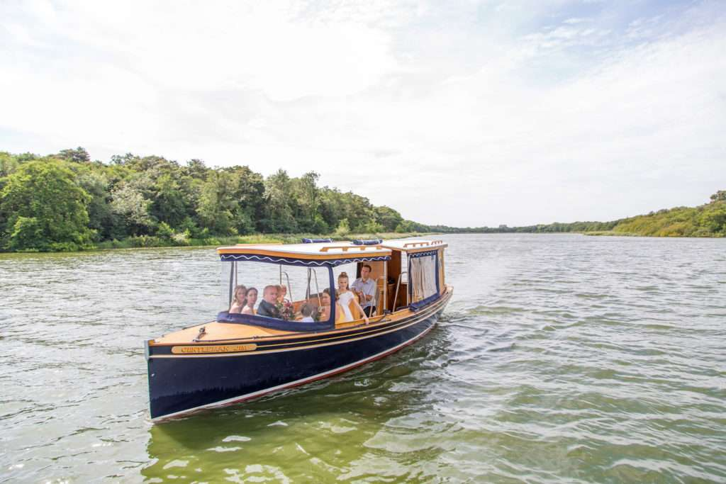 The private boat at The Boat House in Norfolk with the bride, father of the bride and bridal party en-route to the wedding