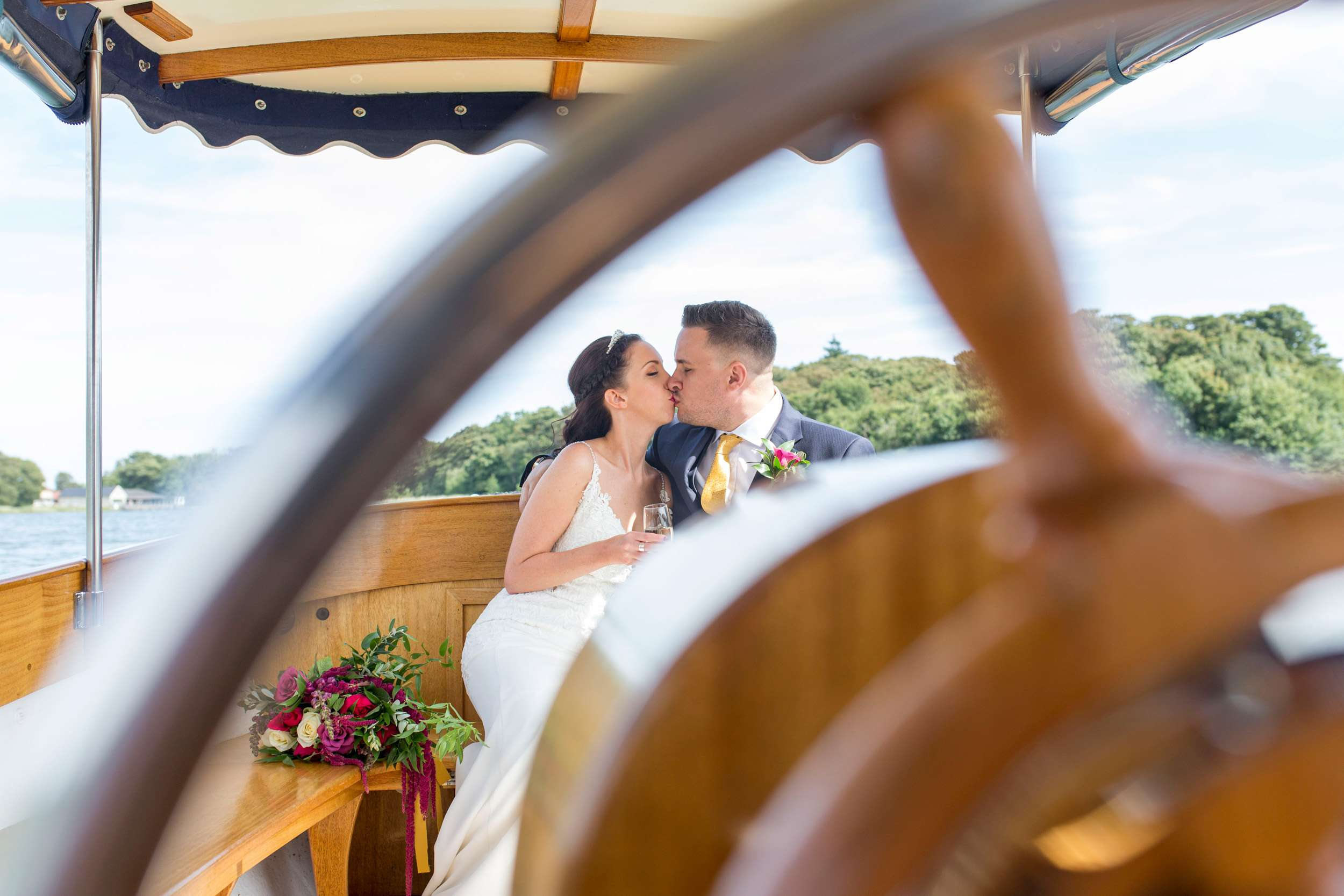 Bride & Groom kissing on the boat at The Boat House wedding. Photo is taken through the steering wheel of the boat