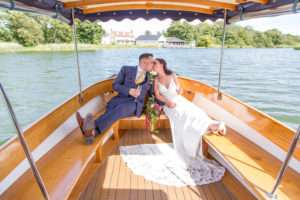 Bride & Groom relaxing on board the boat at The Boat House sharing a kiss and sipping champagne