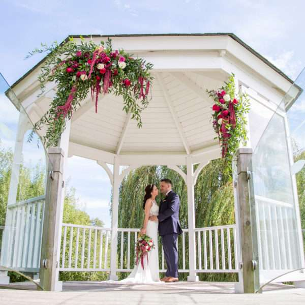 Bride & Groom underneath the pagoda at The Boat House decorated with bold big flower arrangements