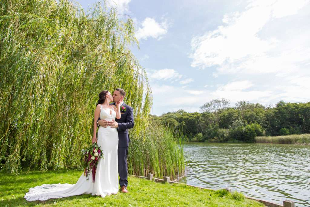 Bride & Groom kissing on the riverbank at The Boat House in Norfolk with the willow tree behind them