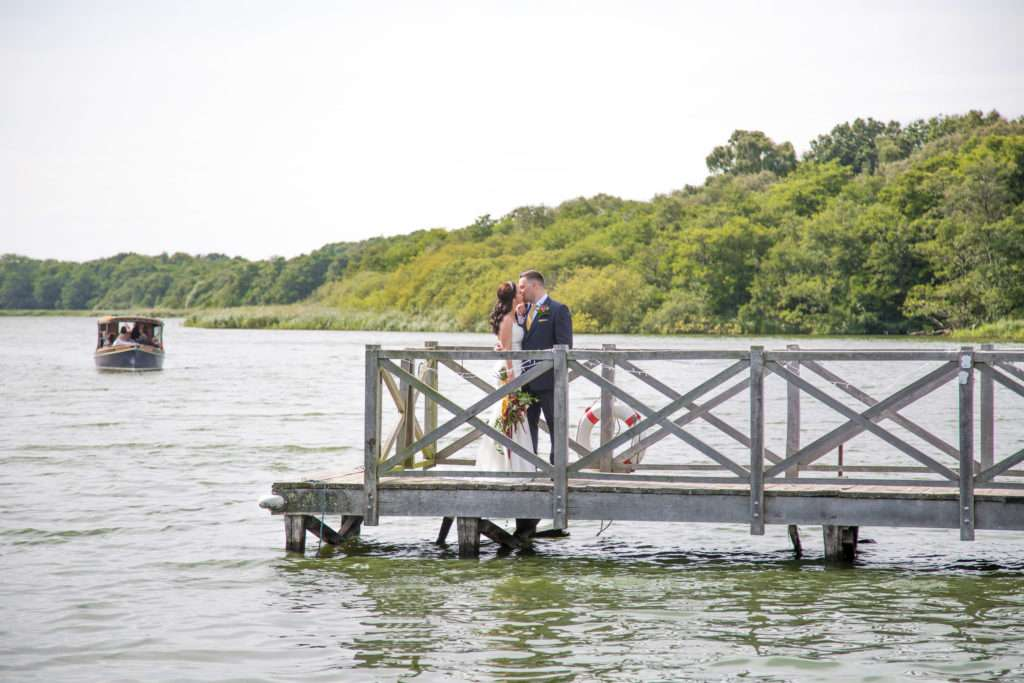Bride & Groom on the pier at The Boat House in Norfolk with the privy boat in the background