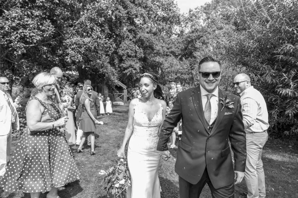 Bride & Groom walking through confetti with wedding guests on either side at The Boat House in Norfolk