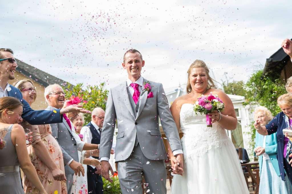 Bride & Groom walking through confetti on their wedding day holding hands