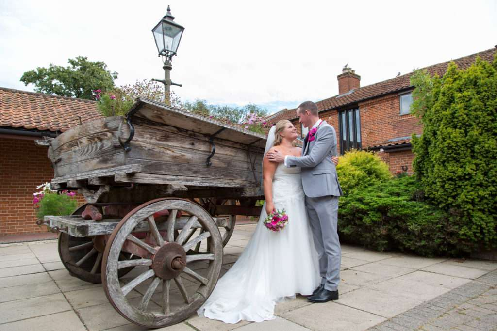 Bride & Groom standing infront of an old cart at Park Farm Hotel in Norfolk