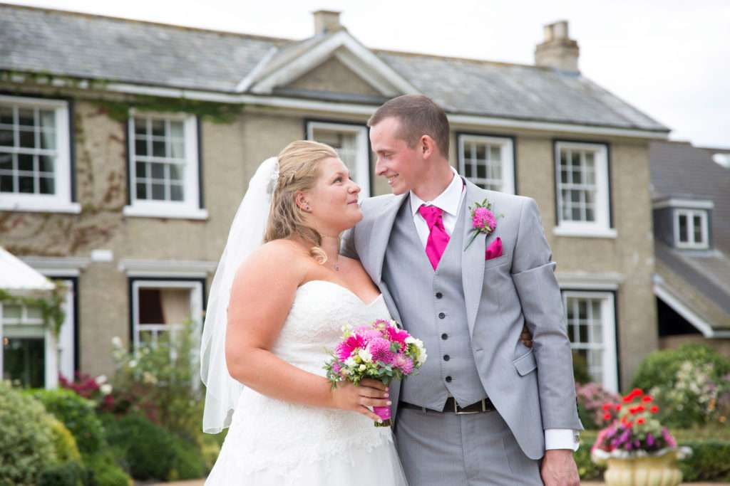 Bride & Groom looking at each with Park Farm Hotel in Norfolk behind  them in the background