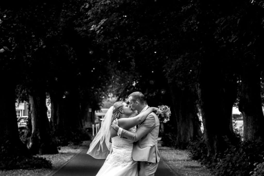 Bride & Groom kissing on the driveway at Park Farm Hotel in Norfolk with the avenue of trees behind them