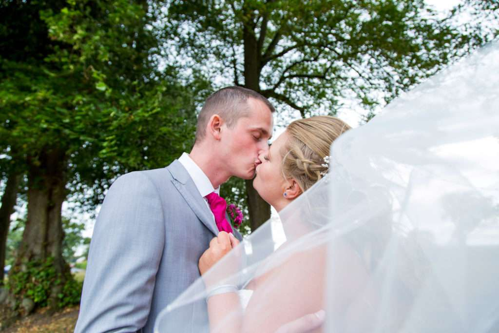 Bride & Groom kissing with trees in the background and the veil blowing in front