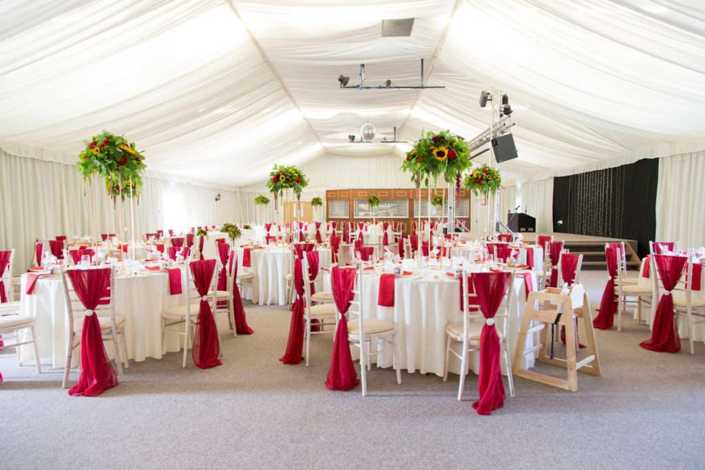 Applewood Hall in Norfolk laid out for a wedding with tables & chairs and red drape chair covers