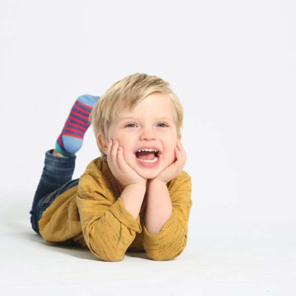 Little boy lying on the floor with his hands holding his head under his chin.