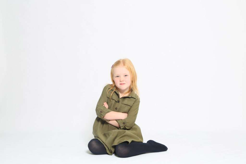 Little girl with arms folded sat down on floor