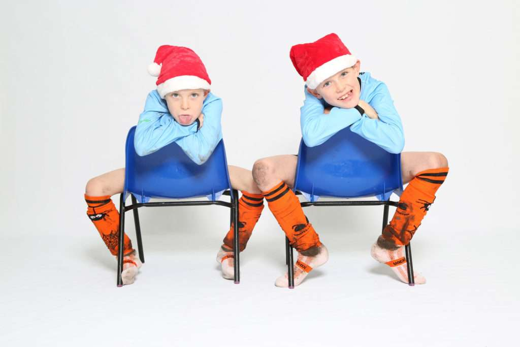 Two boys sat on chairs in their football kits with santa hats on