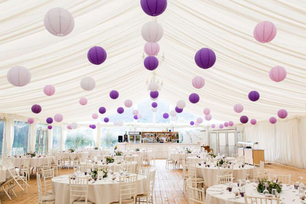 Marquee at Hockwold Hall in Norfolk dressed for a wedding with circular tables and decorated with hanging lanterns
