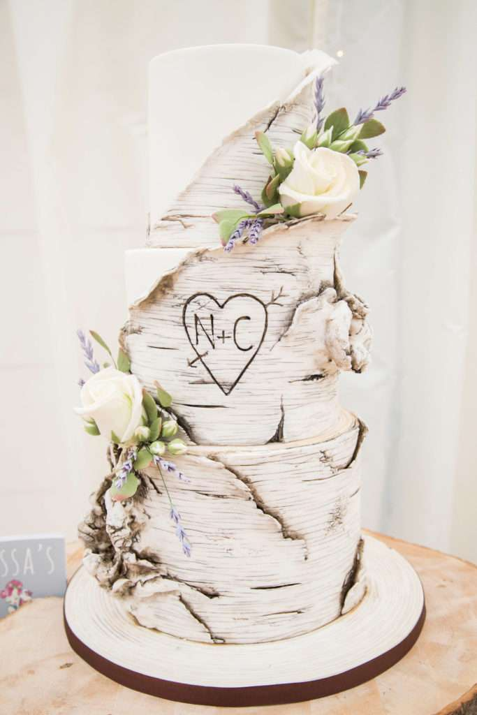 Wedding cakes decorated with white roses with initials N & C in a love heart