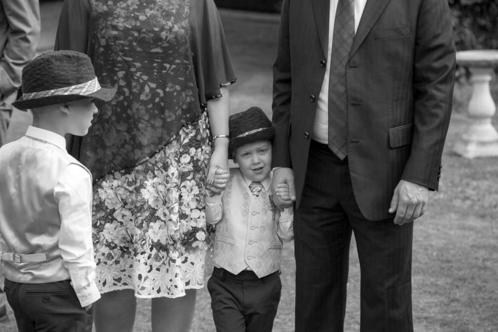 Little boy holding his parents hands at a wedding