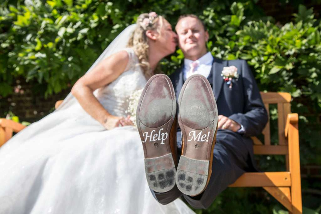 Bride & Groom sitting on a bench. Bride kissing Groom on his cheek. Groom feet up with Help Me written on the soles of his shoes