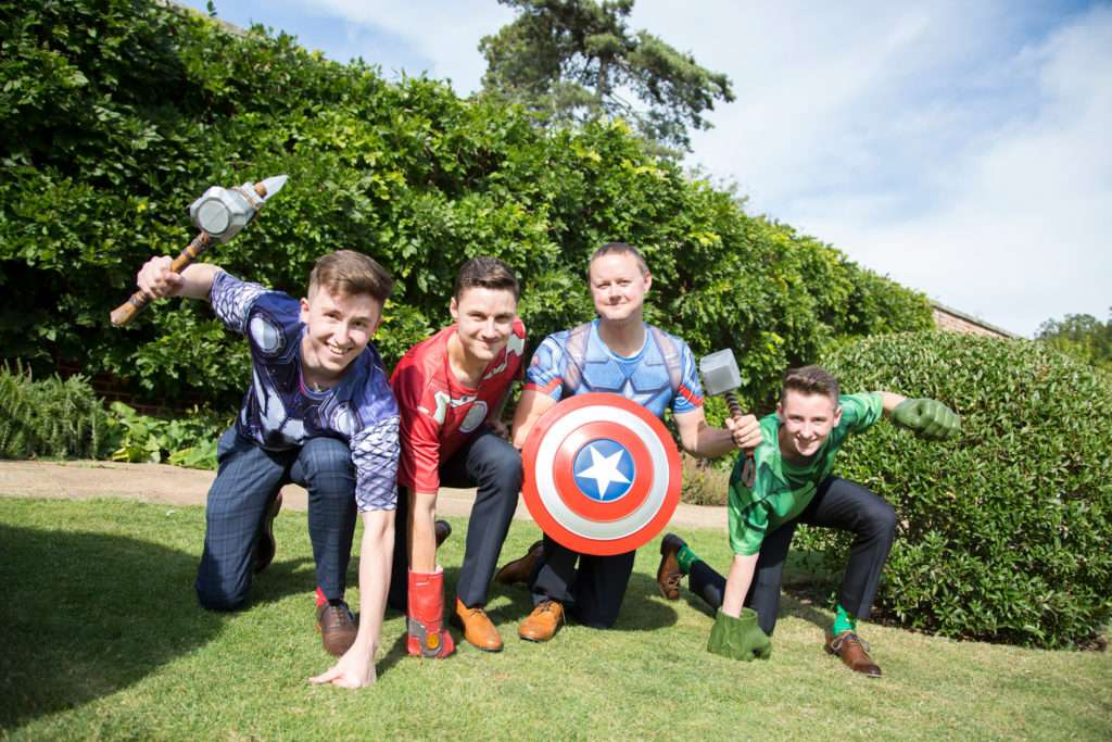 Groom & ushers in super hero t-shirts crouched down on the grass at a wedding