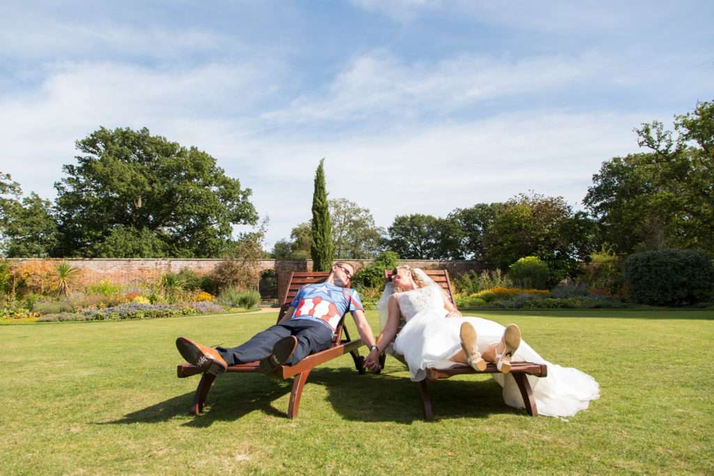 Bride & Groom lounging on sun loungers at Ickworth Hotel in Suffolk